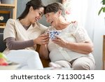 two women laughing together at... | Shutterstock . vector #711300145