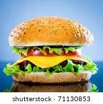 Tasty and appetizing hamburger on a blue background - stock photo
