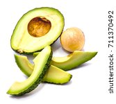 Small photo of Avocado (Persea americana, alligator pear) slices and one half with a stone isolated on white background
