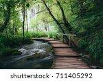 wooden path across small creek... | Shutterstock . vector #711405292