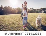 Stock photo beautiful happy family is having fun with golden retriever outdoors mother father and daughter 711413386
