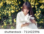 an asian woman who reads in... | Shutterstock . vector #711422596