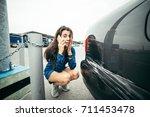 sad woman standing near car... | Shutterstock . vector #711453478