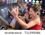 women winning at slot machine | Shutterstock . vector #711590086
