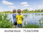 two boys fishing on the lake  | Shutterstock . vector #711621406