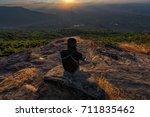 man sitting on mountain cliff... | Shutterstock . vector #711835462