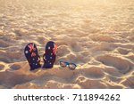 thongs and sunglasses in sand... | Shutterstock . vector #711894262
