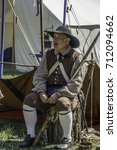 Small photo of WHEATON, IL/USA - SEPTEMBER 9, 2017: A man dressed as a militiaman sits near a tent while conversing with attendees (off camera) at a reenactment of the American Revolutionary War (1775-1783).
