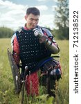 Small photo of A warrior, a nomad in medieval oriental armor, sits on his knee with a small flower in his hand