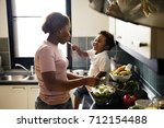 black kid feeding mother with... | Shutterstock . vector #712154488