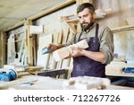 handsome bearded craftsman... | Shutterstock . vector #712267726