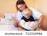 mother holding newborn baby... | Shutterstock . vector #712310986