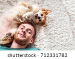 Stock photo the young man with a dog is played close up portrait 712331782