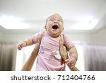 mother reach hand lift up play... | Shutterstock . vector #712404766