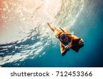 blonde girl making diving in a... | Shutterstock . vector #712453366