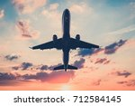 airplane on sunset sky   ... | Shutterstock . vector #712584145