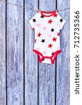 Small photo of Infants cute bodysuit drying on rope. Baby stars print summer romper hanging on clothesline on vintage wooden background, copy space.