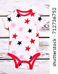 Small photo of Baby high quality soft bodysuit. Newborn baby white stars print romper on old wooden background.