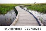 boardwalk curves through  a... | Shutterstock . vector #712768258