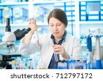 girl laboratory assistant in... | Shutterstock . vector #712797172
