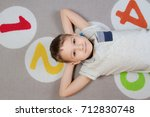 happy kid lying on the floor.... | Shutterstock . vector #712830748