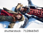 woman and man making snow angel  | Shutterstock . vector #712866565