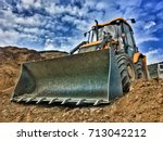 Small photo of Tractor loader backhoe digger loader on a construction site with blue sky and dramatic clouds