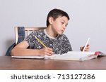 Young teenage boy doing his homework and using his phone - stock photo