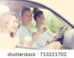 young women traveling by car... | Shutterstock . vector #713221702