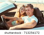young couple traveling by car | Shutterstock . vector #713256172