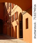 Small photo of Brownish-red walls of a narrow, partly covered alleyway in Bologna
