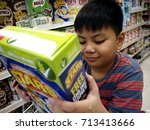 Small photo of ANTIPOLO CITY, PHILIPPINES - SEPTEMBER 10, 2017: A young boy reads the label of a cereal box at a grocery store.
