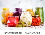Small photo of Sauerkrau, marinated pickles variety preserving jars. Homemade red cabbage beetroot , turmeric yellow kraut, cauliflower, radish, carrots, chili peppers, squash, green beans pickles. Fermented food.