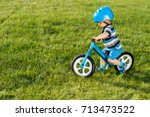 boy in helmet riding a blue... | Shutterstock . vector #713473522