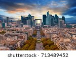 Small photo of La Defense Financial District Paris France at sunset in autumn. Traffic on Champs-Elysees with green trees aside. Modern vs. Old architecture