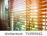 wooden blinds with sun rays. | Shutterstock . vector #713503162