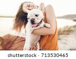 Stock photo happy hipster woman playing with bulldog on the beach in sunset light summer vacation stylish 713530465