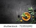 Small photo of Black and green olives and oil in wooden bowl on black slate background. Top view with space for text.