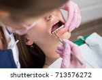 female dentist checking up... | Shutterstock . vector #713576272