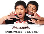 Happy asian boys grabbing a cake - stock photo
