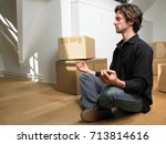 man doing yoga with moving boxes   Shutterstock . vector #713814616