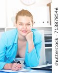 Small photo of Office worker woman is signing agreement papers of financial nature at office.