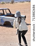 Small photo of A female taking a photo of an old chassis of a vintage personal vehicle near the town of solitaire in Namibia Southern Africa in the desert at a nearby service station