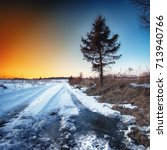 Small photo of Wheel tracks in mire at winter. Sunset nime