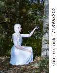 Small photo of Attractive young woman with long blond hair in white dress kneeling holding a crystal ball aloft in her hand in an enchanted forest in a conceptual spiritual image