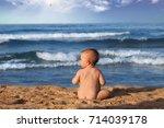 baby boy sitting on the beach...   Shutterstock . vector #714039178
