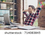 Small photo of Cheerful young brunet guy is watching at his laptop screen, at his work place, with arms behind the head, resting, smiling, in the office