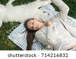 young woman resting with a dog... | Shutterstock . vector #714216832