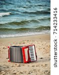 Small photo of A red accordion on a beach
