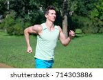 man running on sunny summer day ... | Shutterstock . vector #714303886